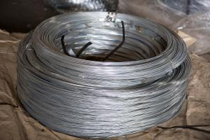Tension wire coil for barbed wire mounting