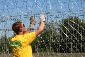 Installation of a Concertina razor mesh on a metal fence